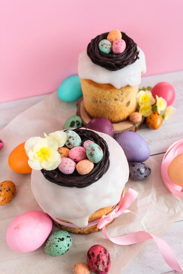 Easter traditional cake with chocolate nest, candy and quail eggs decoration blossom flowers, colorful spring stillife in soft lig. Ht and trendy pastel colors royalty free stock photo