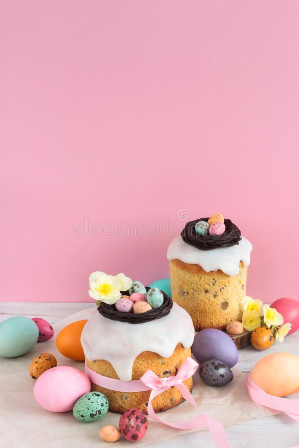 Easter traditional cake with chocolate nest, candy and quail eggs decoration blossom flowers, colorful spring stillife in soft lig. Ht and trendy pastel colors stock image