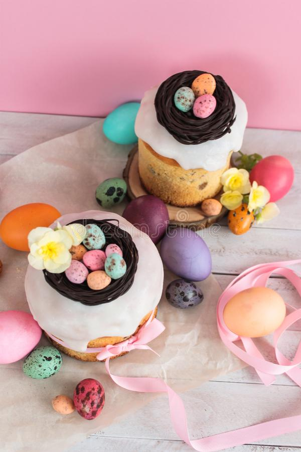 Easter traditional cake with chocolate nest, candy and quail eggs decoration blossom flowers, colorful spring stillife in soft lig. Ht and trendy pastel colors stock photos