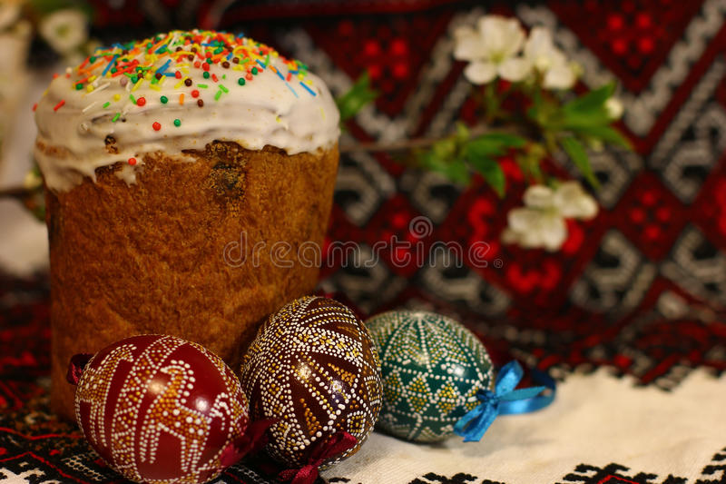 Easter traditional. Easter decorated eggs and homemade breads on the traditional tablecloth background. Spring of flowering tree stock image