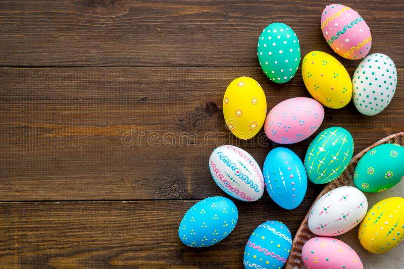 Easter traditions. Colorful Easter eggs in basket on dark wooden background top view space for text royalty free stock image