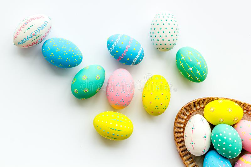 Easter traditions. Colorful Easter eggs in basket on white background top view royalty free stock image