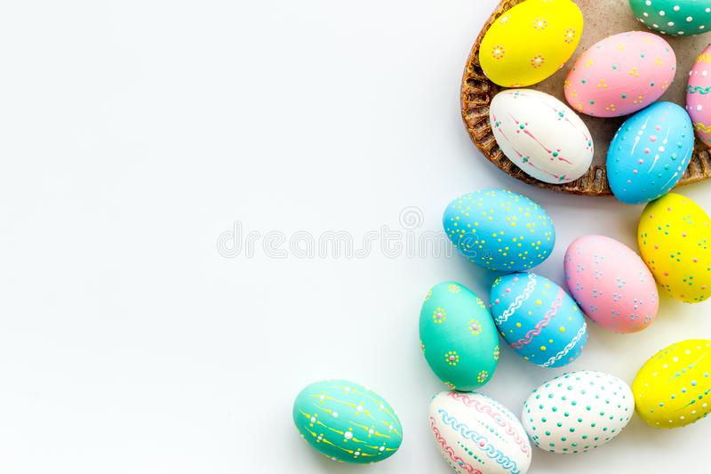 Easter traditions. Colorful Easter eggs in basket on white background top view copy space border royalty free stock images