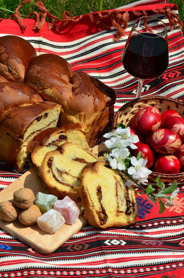 Easter traditions: painted eggs and pound cake. Traditional painted eggs, nuts pound cake and red wine for Easter royalty free stock images