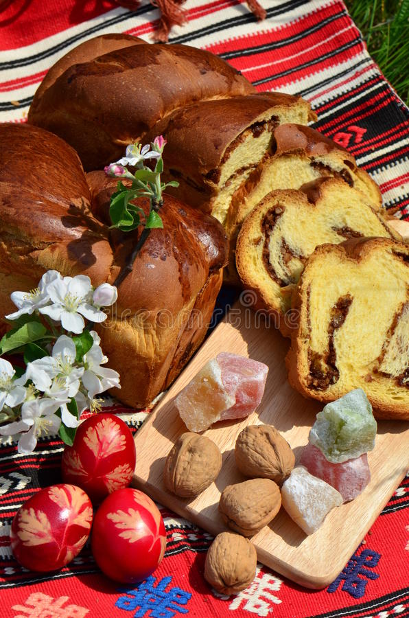 Easter traditions: painted eggs and pound cake. Traditional painted eggs, nuts pound cake and red wine for Easter royalty free stock image