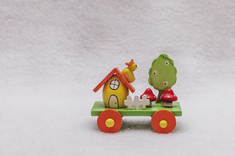 Easter train and egg-house, duckling, mushrooms, a tree in flowers and a white fence - wooden holiday transport toy. Yellow, green, red and orange colors royalty free stock images