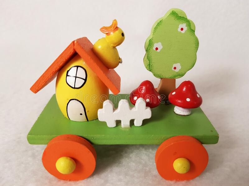 Easter train and egg-house, duckling, mushrooms, a tree in flowers and a white fence - wooden holiday transport toy. Yellow, green, red and orange colors stock photo