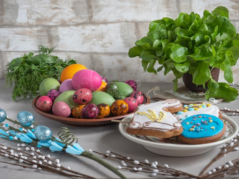 Easter treat of colored eggs, painted gingerbread, fresh herbs, and willow twigs royalty free stock image