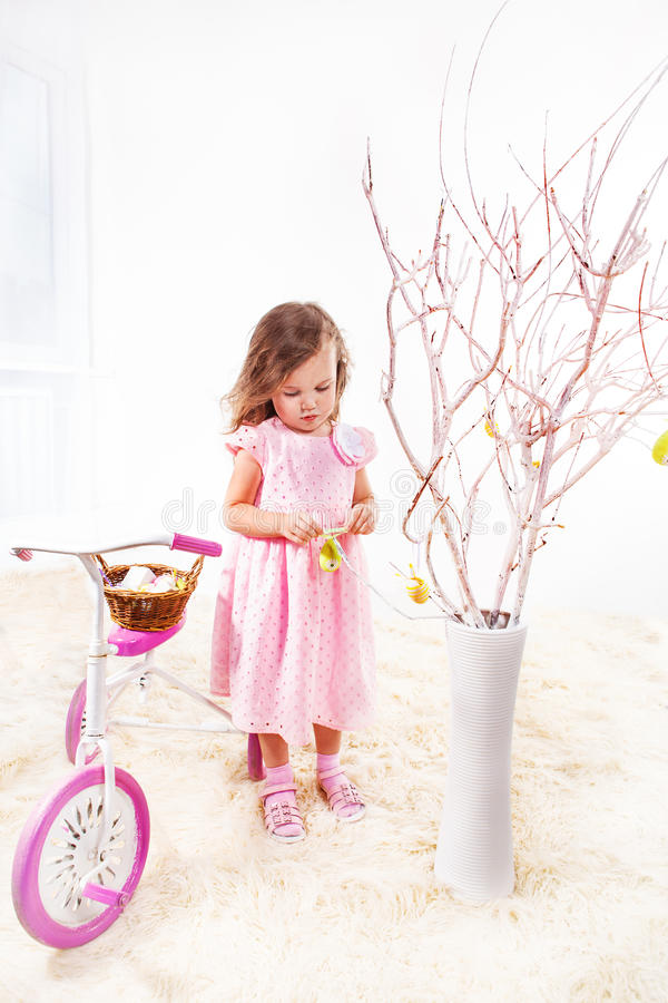 Easter tree. Preschool girl in pink dress decorating Easter tree stock images