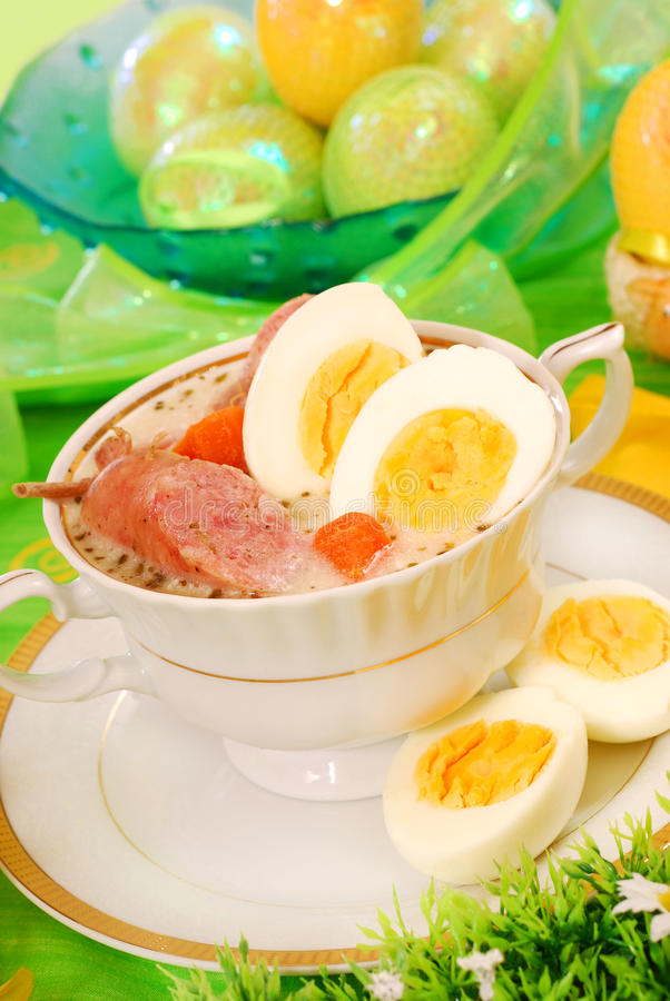 Easter white borscht ( zurek ). Traditional polish white borscht with eggs and sausage in white dishware for easter royalty free stock images