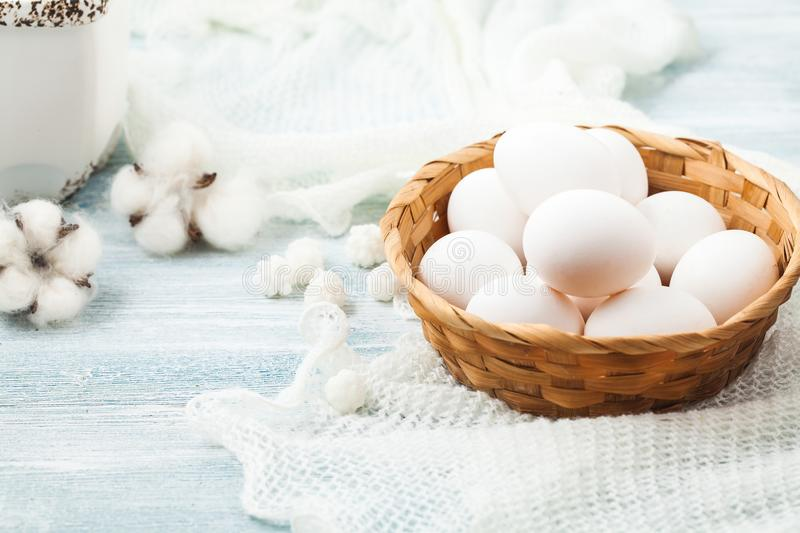 Easter white eggs in a wicker basket on a light background Background for a postcard stock photo