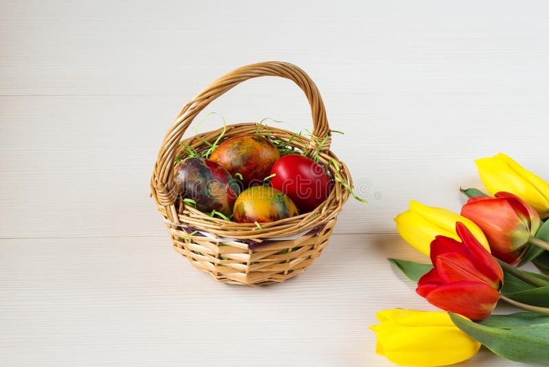 Easter wicker basket with colored eggs and yellow and red tulips on white wooden board. stock photos