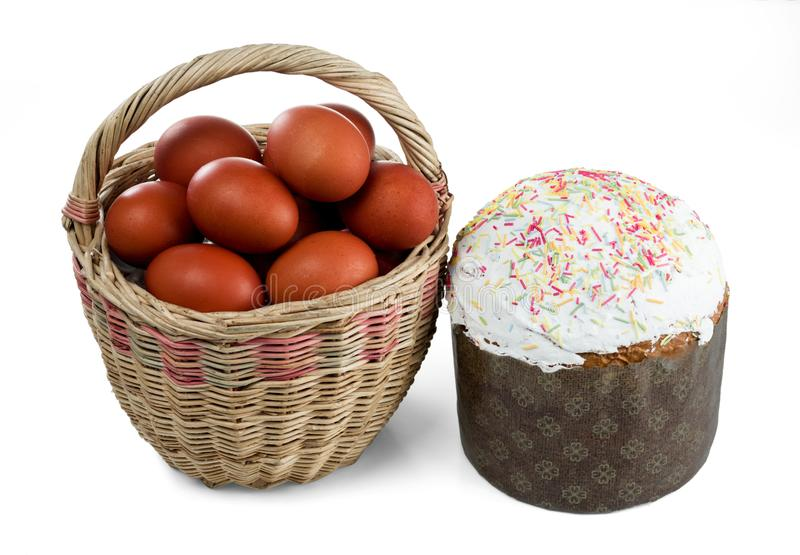 Easter wicker basket with kulich and dyed red Easter eggs isolated on a white stock photo