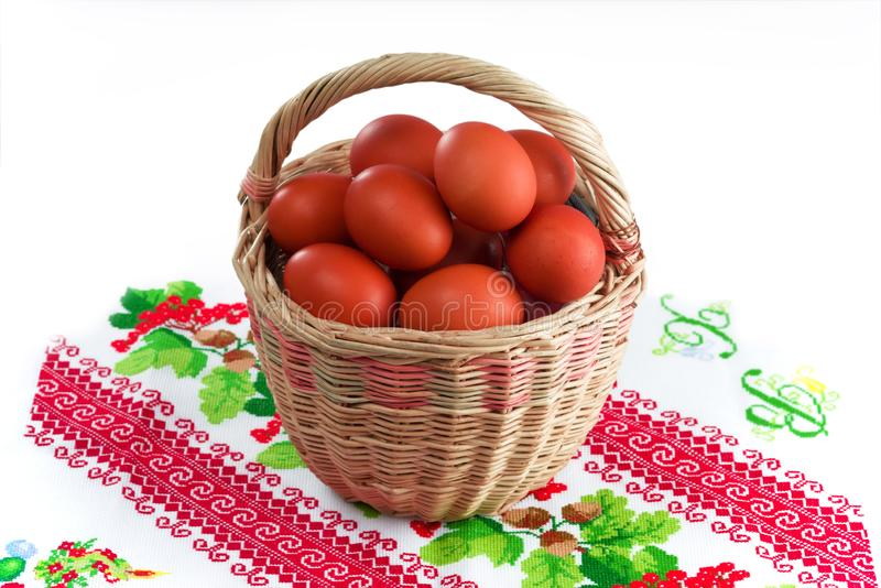 Easter wicker basket with red Easter eggs on a white background stock photography