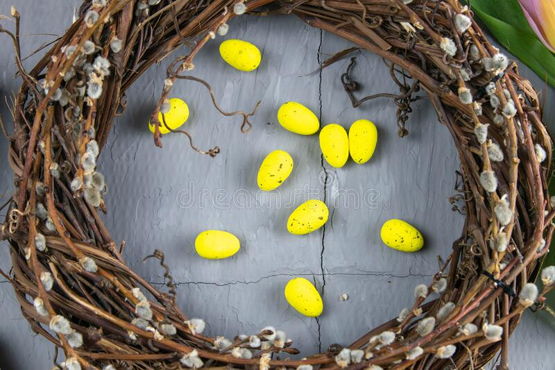 Easter willow wreath and blue Easter eggs on blue background. Top view, copy space stock image