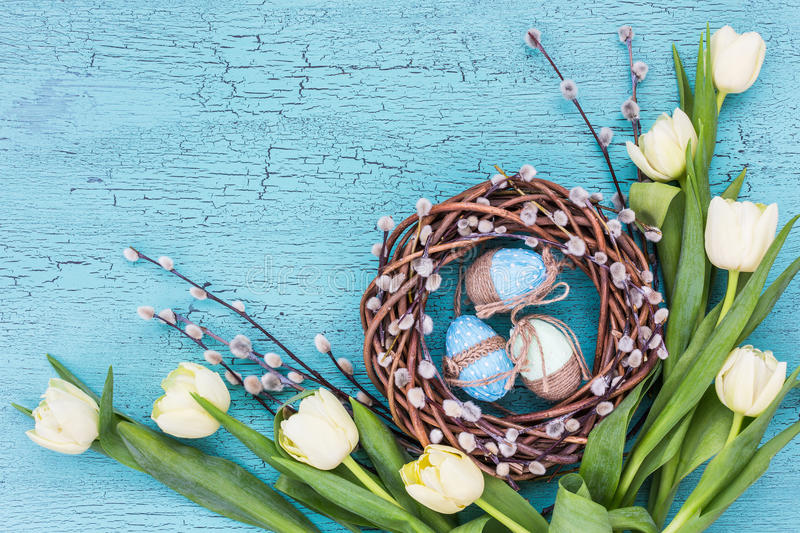Easter willow wreath, white tulips and blue Easter eggs on blue background. Top view, copy space royalty free stock photos