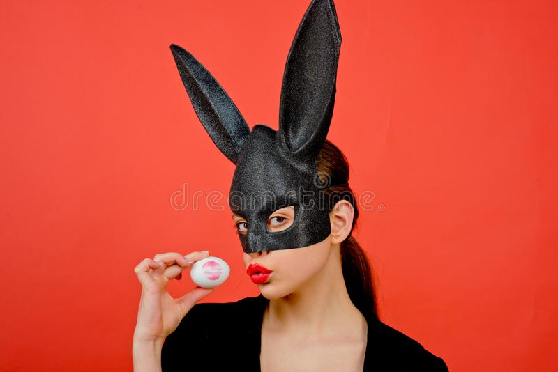 Easter woman. Woman rabbit, easter bunny girl. Red lip imprint on easter egg on red background. Female mouth kiss. Print. Of red lips on white egg stock photo