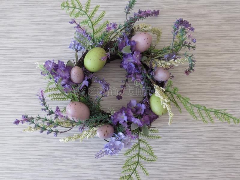 Easter wreath of green blue purple flowers and colorful eggs on grey background. Quail eggs. stock photo