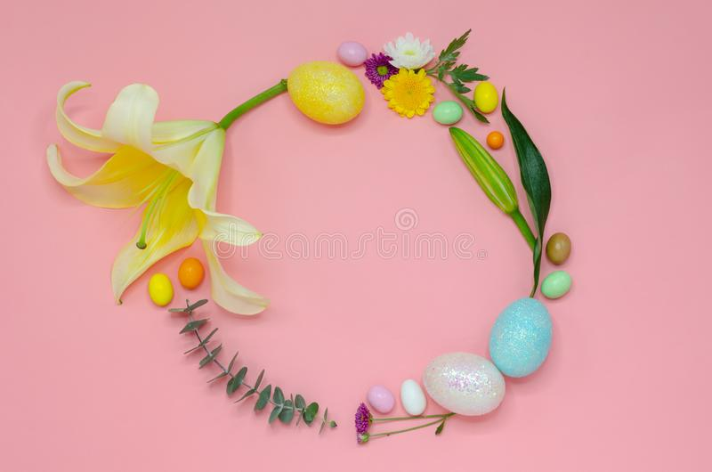 Easter wreath layout made of colorful glitter eggs and flowers stock photo