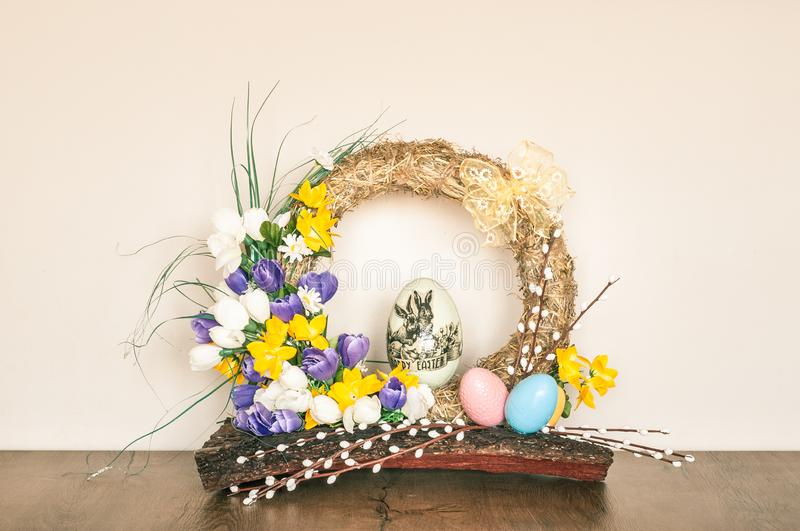 Easter Wreath Made of Hay with Artificial Flowers and Eggs royalty free stock image