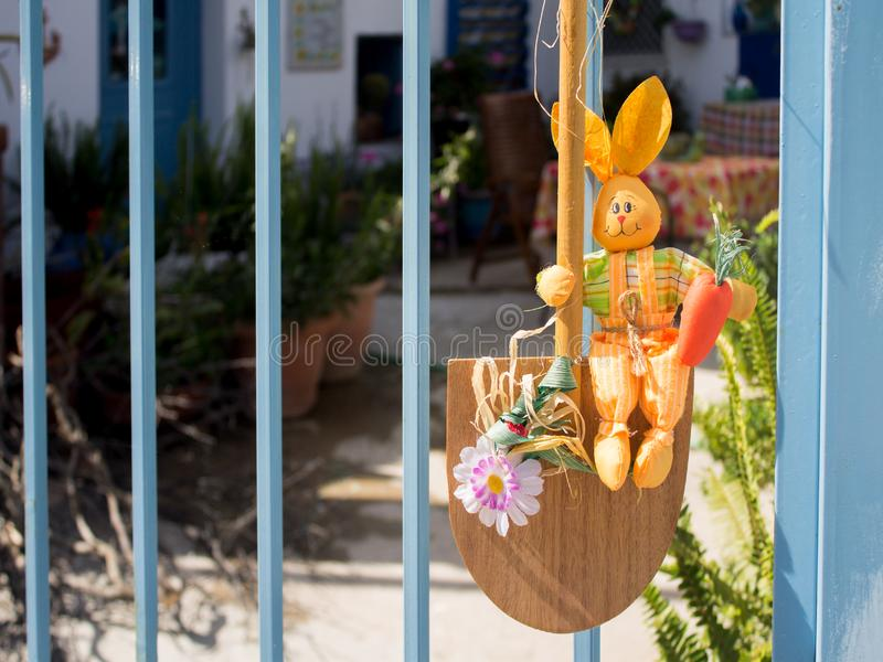 Easter yellow rabbit sitting on a shovel at the entrance to the yard stock photography