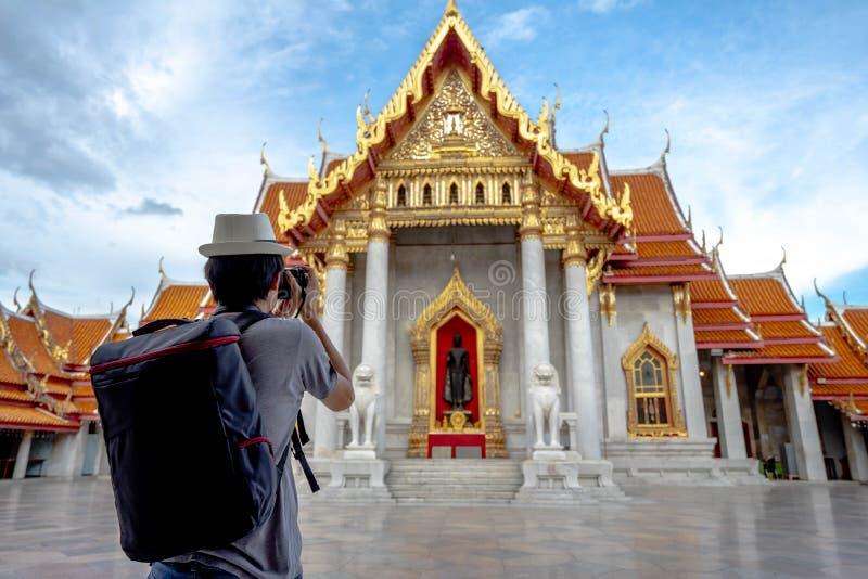 Eastern Asia summer holidays. Asian man tourist taking photos with cameras at Wat Benchamabopitr Dusitvanaram Bangkok Thailand. Travelers take pictures with stock image