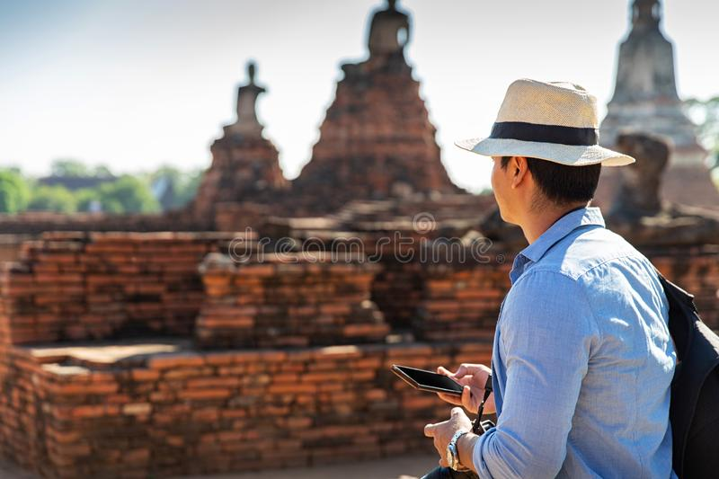 Eastern Asia summer holidays. Caucasian man tourist from back looking at Wat Chaiwatthanaram temple. Tourist travel in the morning. At temple in old city of royalty free stock image