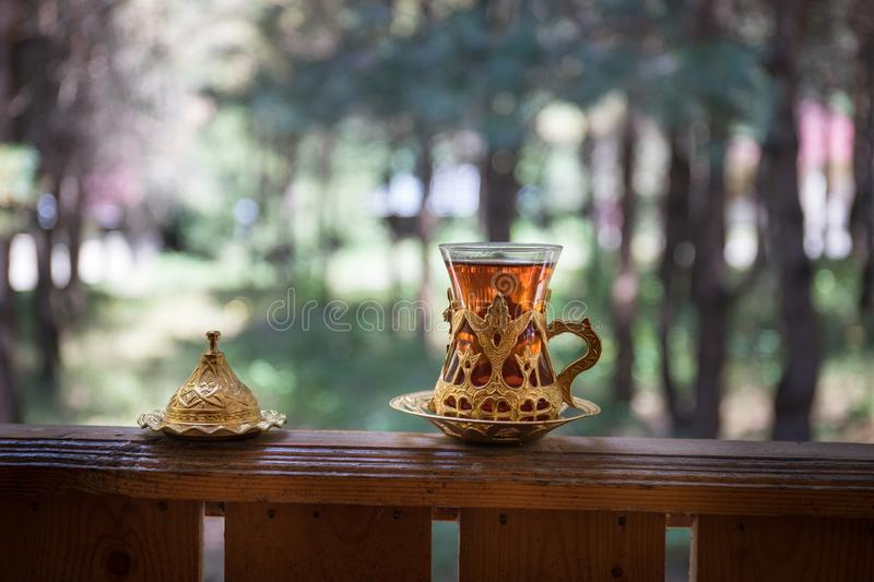 Eastern black tea in glass at the forest. Eastern tea concept. Armudu traditional cup. Green nature background royalty free stock image