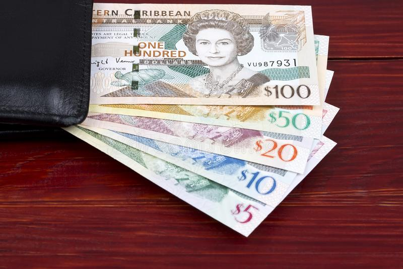 Eastern Caribbean dollars in a black wallet. On a wooden background stock photos