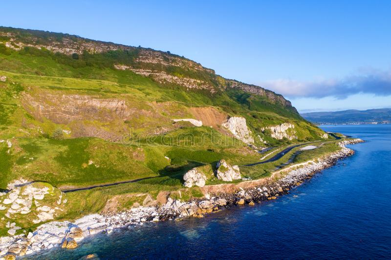 Antrim Coastal Road in Northern Ireland, UK. The eastern coast of Northern Ireland and Antrim Coast Road, a.k.a. Giant`s Causeway Coastal Route with a cars royalty free stock photography