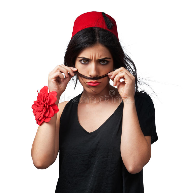 Eastern Fashion Concept. Isolated photo of a beautiful young girl as a tomboy. She holds her hair as a moustache and she wears a red hat. The hat is called Fes royalty free stock photos