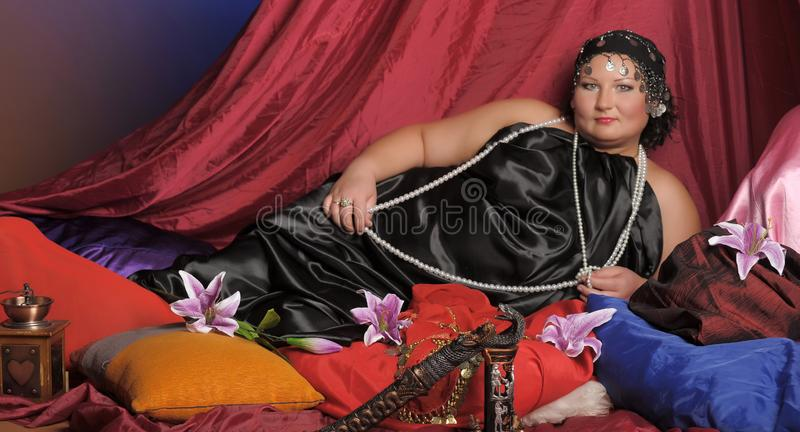 Eastern Guria, a well-fed woman in Oriental clothes lies royalty free stock images