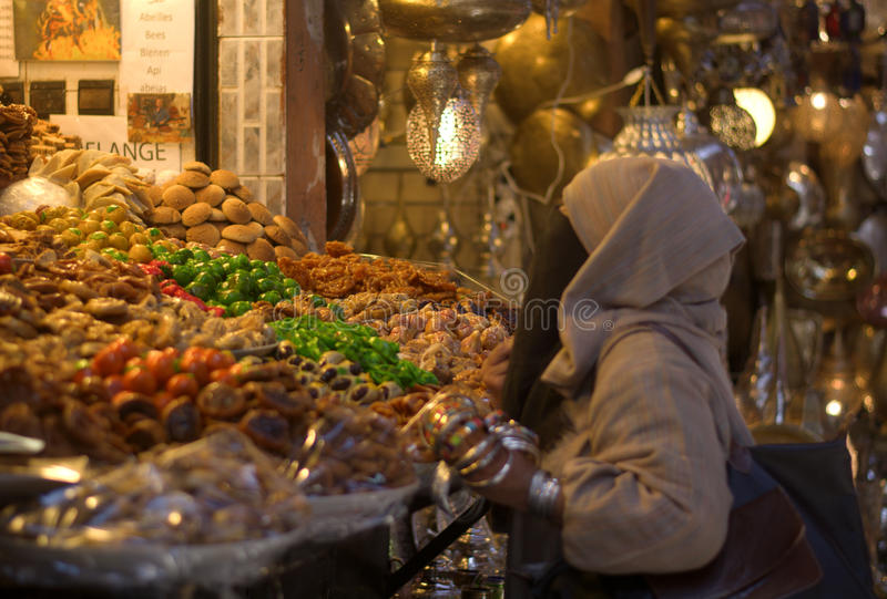 Arabian woman doing the expense of sweets and dried fruits. The bright colors of the Eastern markets royalty free stock photography