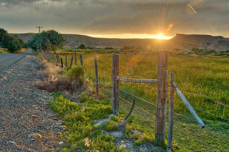 Sunset over the high desert hills on the horizon. Eastern Oregon Sunset over the high desert hills on the horizon on the other side of a barbed wire fenced royalty free stock photography
