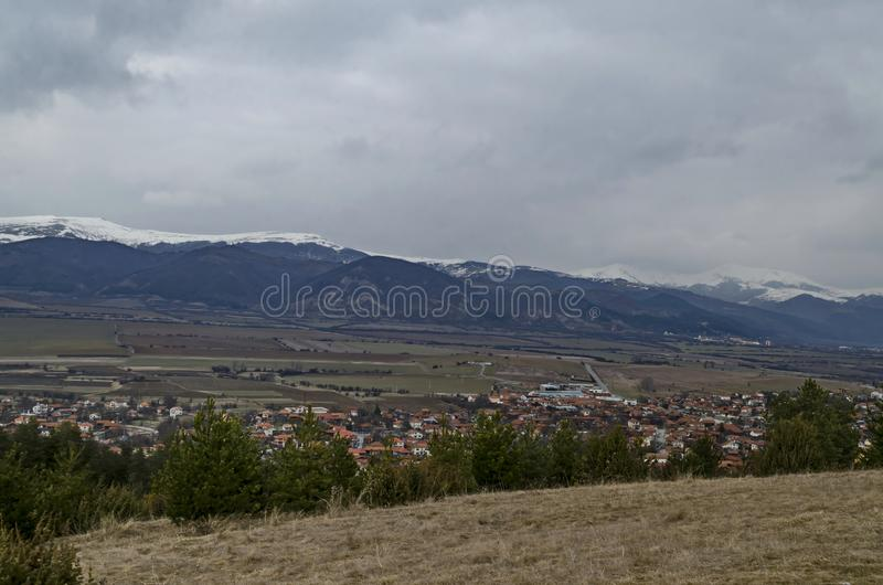 Eastern part of the Zlatitsa Pirdop valley and residential district of  village Chavdar in background of the snowy Balkan mountain. Sofia, Bulgaria, Europe royalty free stock images