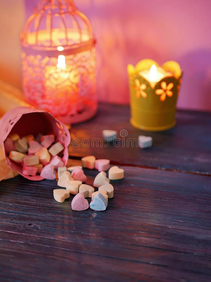 Eastern sweets, dates, vitamin hearts on a plate on a blue wooden table, decorative lantern, burning candles royalty free stock image