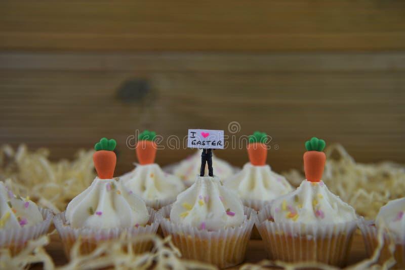Eastertime cupcakes με τις διακοσμήσεις καρότων και ένα μικροσκοπικό ειδώλιο προσώπων που κρατά ένα σημάδι για την αγάπη Πάσχα στοκ φωτογραφία