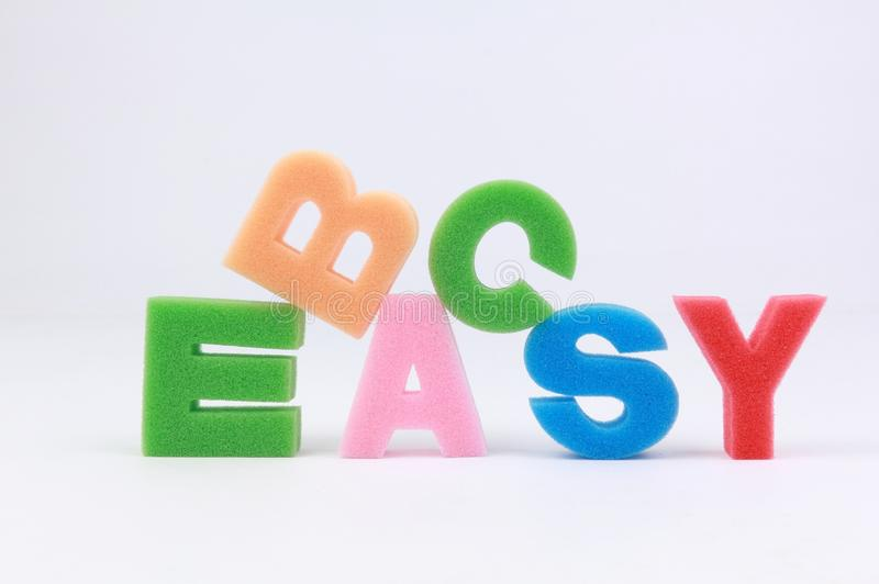 Easy as ABC. Easy word spelled out with concept of easy as ABC on white background stock photos