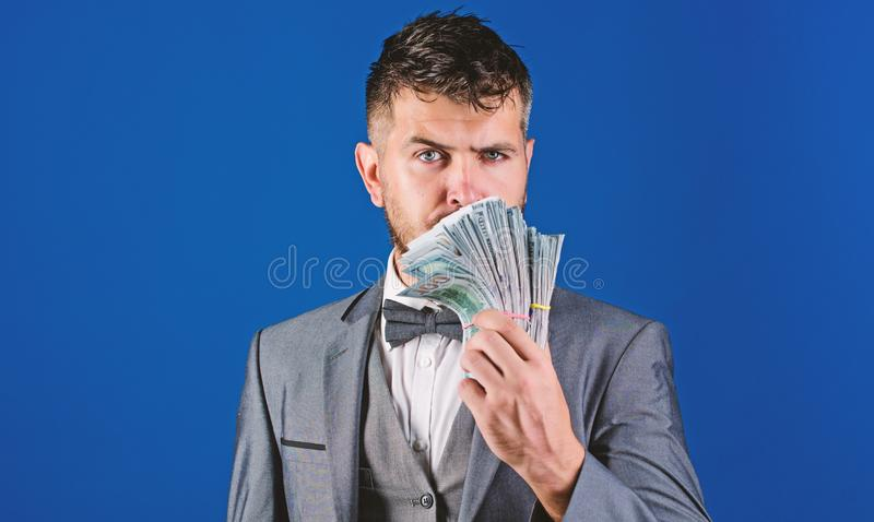 Easy cash loans. Man formal suit hold pile of dollar banknotes blue background. Businessman got cash money. Richness and royalty free stock images