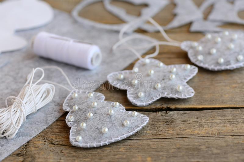 Easy Christmas craft and toys idea. Gray felt fir tree, ball and star decorated with white beads, craft supplies on vintage wooden. Christmas felt crafts stock image