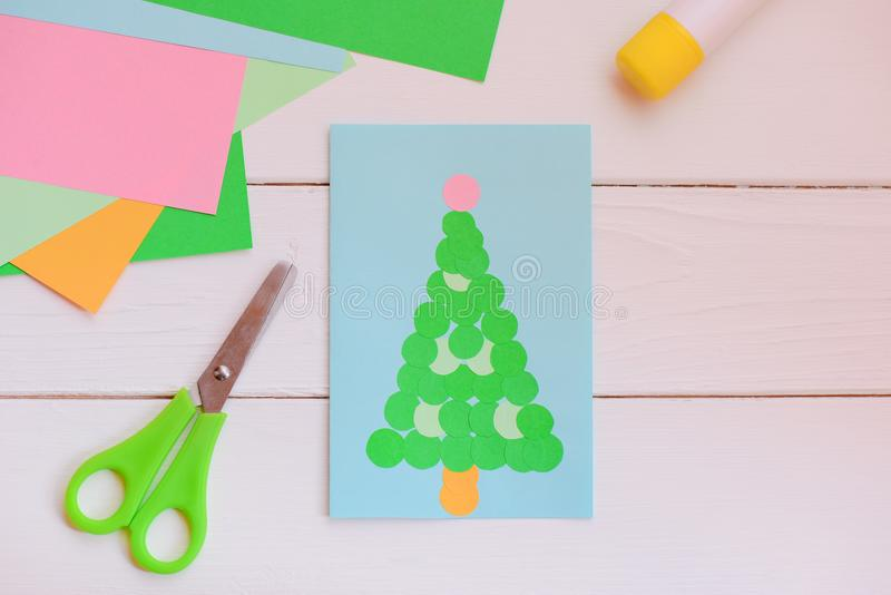 Paper Christmas greeting card made of simple geometric shapes, colored paper set, scissors, glue stick on a wooden table. Easy Christmas crafts to make royalty free stock photo