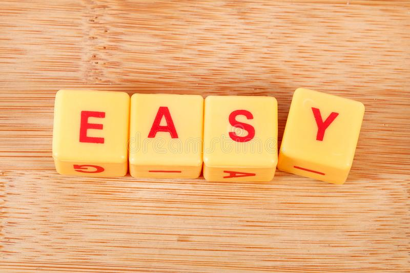 Easy. Concept shot of easy spelled on wooden background royalty free stock photography