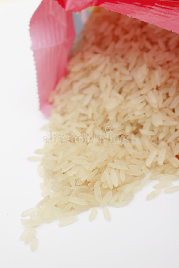 Easy cook rice. American easy cook rice spilling from packet on a white background royalty free stock photos