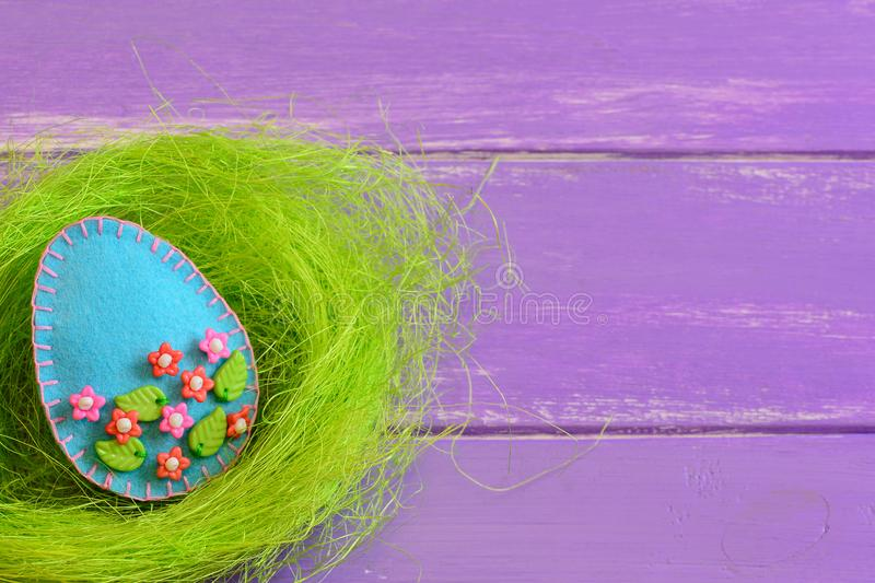 Felt Easter egg in the nest on the purple wooden background with empty space for text. Beautiful spring Easter card. Happy Easter. Easy Easter crafts. Idea for stock images