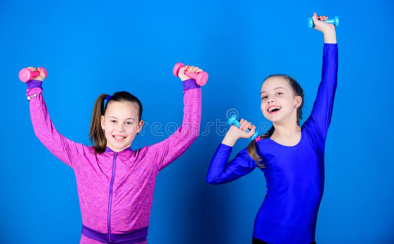 Easy exercises with dumbbell. Sporty upbringing. On way to stronger body. Girls exercising with dumbbells. Beginner. Dumbbells exercises. Children hold stock photography