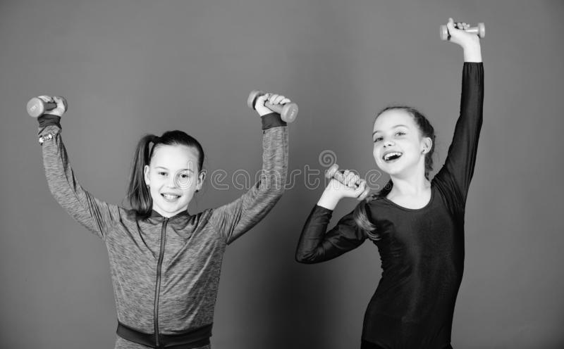 Easy exercises with dumbbell. Sporty upbringing. On way to stronger body. Girls exercising with dumbbells. Beginner. Dumbbells exercises. Children hold royalty free stock image