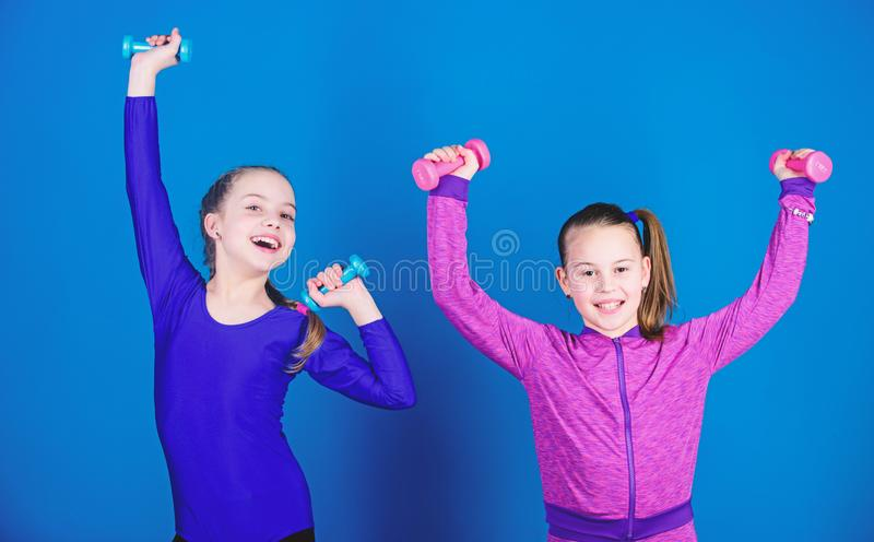 Easy exercises with dumbbell. Sporty upbringing. On way to stronger body. Girls exercising with dumbbells. Beginner. Dumbbells exercises. Children hold stock photos