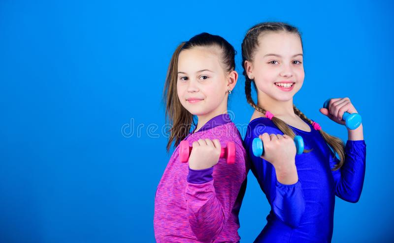 Easy exercises with dumbbell. On way to stronger body. Girls exercising with dumbbells. Beginner dumbbells exercises. Sporty upbringing. Children hold royalty free stock photos