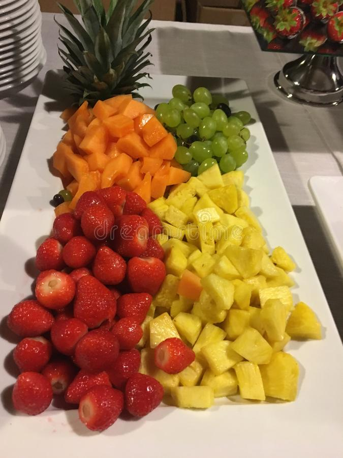Tray of fresh fruit with pineapple, strawberries, melon, grapes stock images