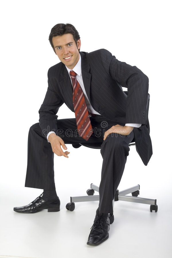 Easy going. Smiling, handsome businessman. Seating on chair. Looking at camera. White background stock photo